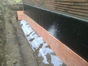 Waterproofed wall, membrane on, gravel cloth in and drainage board on